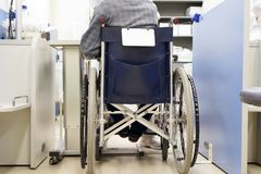 Old man sitting on wheelchair in hospital stock image