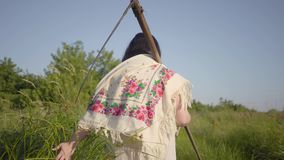Back view of overweight woman in traditional shawl walking on summer field with the scythe after hard working day. Back view of Slavic overweight woman in stock video