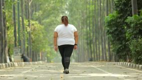 Back view of overweight woman walking at park