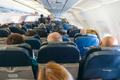 Back view of passengers on chairs inside aircraft.  Royalty Free Stock Images