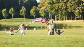 Back view patriotic family running with background. Rear view soldier with wife holding background and moving to the park lake with kids stock video
