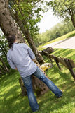 Back view of a peeing man in the nature Royalty Free Stock Photo