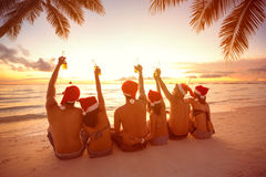 Back view of people with Santa hats sitting on beach. Back view of group people with raised hands holding a bottle of beer on beach, Christmas holiday Royalty Free Stock Photos