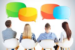 Back view of people with speech bubbles. Back view of young businessmen and women sitting on chairs on gray background with empty speech bubbles Royalty Free Stock Photos