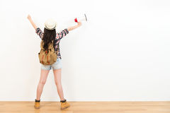 Back view photo of beautiful sweet backpacker. Woman holding loudspeaker and raised hands celebration holiday travel vacation standing on wood floor with white Royalty Free Stock Photos