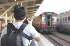 Back view of photographer taking a picture in train station. Selective focus and shallow depth of field. Royalty Free Stock Image