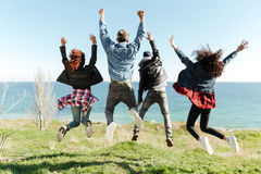 Back view picture of a group of friends jumping. Outdoors near beach with raised hands Royalty Free Stock Photos