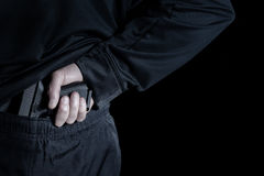 Back view of pistol being pull out of pants by male hand Royalty Free Stock Image