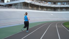 Overweight female jogging on city stadium track. Back view of plus size woman jogger in sporty outfit running along stadium track during intense cardio workout stock video