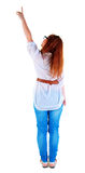 Back view of pointing beautiful redhaired  woman . Young girl in  jeans.  Rear view people collection.  backside view of person.  Isolated over white Royalty Free Stock Photography
