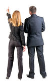 Back view of  pointing business team. Young couple (man and woman) .  beautiful friendly girl and guy in suit together. Rear view people collection.  backside Royalty Free Stock Photography