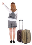 Back view of  pointing business woman with suitcase looking up. Royalty Free Stock Image