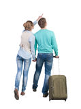 Back view of pointing couple with  green suitcase looking up. Stock Photos