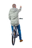 Back view of pointing man with a bicycle. Royalty Free Stock Photo