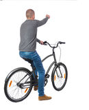 Back view of pointing man with a bicycle. cyclist sits on the bike. Stock Images
