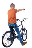 Back view of pointing man with a bicycle. Stock Image