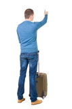 Back view of  pointing man  with suitcase. Stock Images
