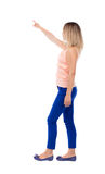 Back view of pointing walking  woman. Going girl pointing.  backside view of person.  Rear view people collection. Isolated over white background. Girl in blue Royalty Free Stock Photos