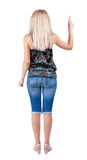 Back view of pointing woman. Beautiful blonde girl in jeans. Rear view people collection. backside view of person. Isolated over white background. Girl in royalty free stock images