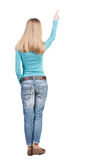 Back view of  pointing woman. beautiful blonde girl. Rear view p Royalty Free Stock Photo