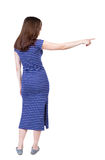 Back view of  pointing woman. Beautiful girl. Rear view people collection.  backside view of person.  Isolated over white background. A girl in a long blue Stock Images