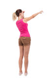 Back view of  pointing woman. Beautiful girl. Rear view people collection.  backside view of person.  Isolated over white background. Blonde in brown shorts Stock Photography