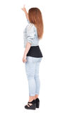 Back view of  pointing woman. beautiful redhead girl in jeans. Stock Images