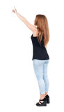 Back view of  pointing woman. beautiful redhead girl in jeans. Royalty Free Stock Photography