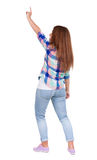 Back view of  pointing woman. beautiful redhead girl in jeans. Royalty Free Stock Images