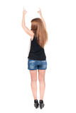 Back view of  pointing woman. beautiful redhead girl in shorts. Royalty Free Stock Image