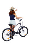 Back view of pointing woman with a bicycle. Royalty Free Stock Photo