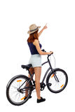 Back view of pointing woman with a bicycle. Stock Images