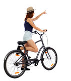 Back view of pointing woman with a bicycle. cyclist sits on the bike. Stock Images