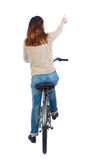 Back view of pointing woman with a bicycle. Royalty Free Stock Images
