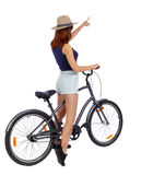 Back view of pointing woman with a bicycle. Stock Photography