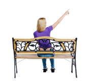 Back view of pointing woman sitting on a bench. Stock Image