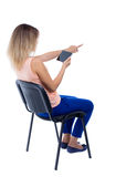 Back view of pointing woman sitting on chair and looks at the sc Stock Photo