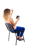 Back view of pointing woman sitting on chair and looks at the sc Stock Photography