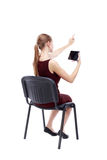 Back view of pointing woman sitting on chair and looks at the sc Royalty Free Stock Photography