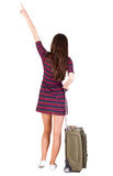 Back view of  pointing woman with suitcase looking up Stock Photo