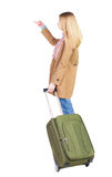 Back view of  pointing woman with suitcase looking up. Stock Photography