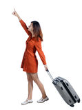 Back view of pointing woman with suitcase looking up. Stock Photo