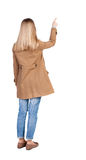 Back view of  pointing womanin brown cloak. Royalty Free Stock Photo