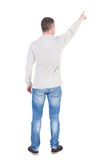 Back view of  pointing young man in  shirt and jeans. Stock Photo