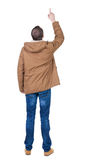 Back view of  pointing young men in parka. Royalty Free Stock Photo