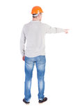 Back view of  pointing young men in  shirt and helmet. Stock Photo