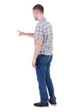 Back view of  pointing young men in  shirt and jeans. Royalty Free Stock Images