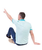 Back view of  pointing young men in  shirt and jeans. Stock Photo