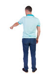 Back view of  pointing young men in  shirt and jeans. Stock Image
