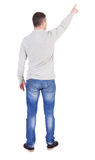Back view of  pointing young men in  shirt and jeans. Royalty Free Stock Photo